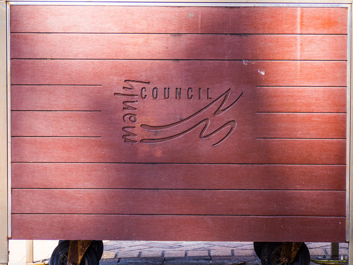 Manly Council etched in to the side of this trolley unit Council Logo Manly Council Part Of Text Wood - Material