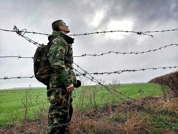 Young Army Soldier Standing By Fence On Field