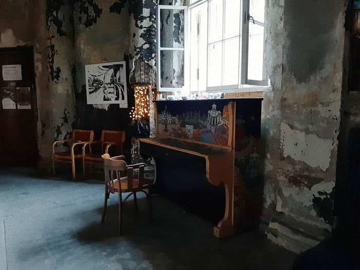Empty chairs and table in abandoned building