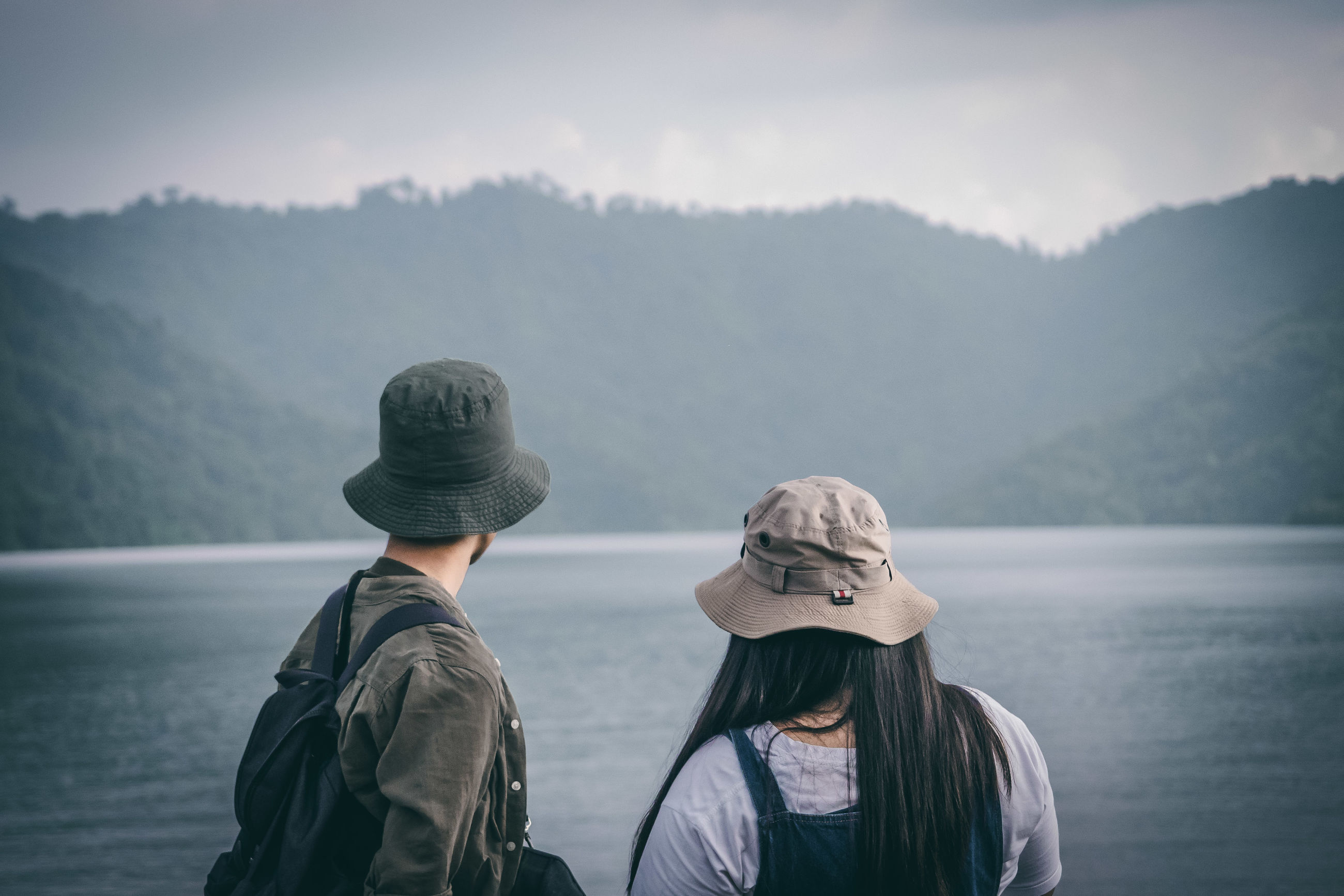 REAR VIEW OF WOMEN LOOKING AT LAKE AGAINST MOUNTAIN RANGE