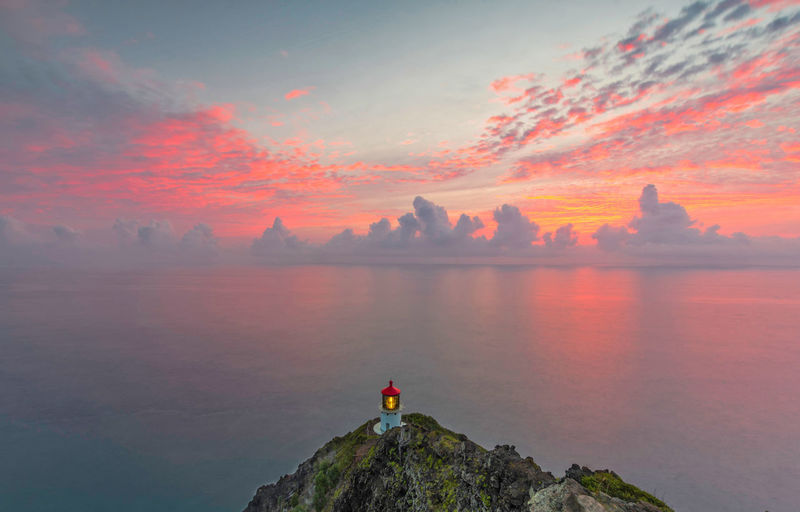 Photo taken at Makapu'u lighthouse, HI Hawaii Lighthouse Oahu Beauty In Nature Cloud - Sky Idyllic Leisure Activity Nature Non-urban Scene One Person Orange Color Outdoors Rock Rock - Object Scenics - Nature Sky Solid Standing Sunrise Tranquil Scene Tranquility Water