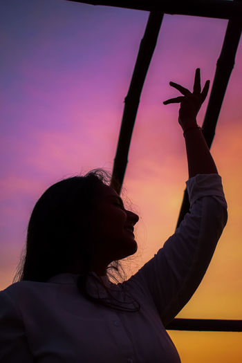 Portrait of silhouette woman with arms raised against sky during sunset