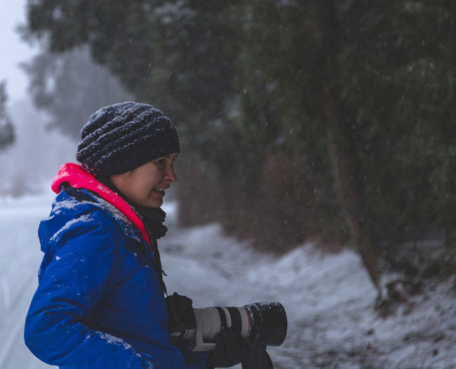 Side view of woman wearing warm clothing while holding digital camera in forest during snowfall