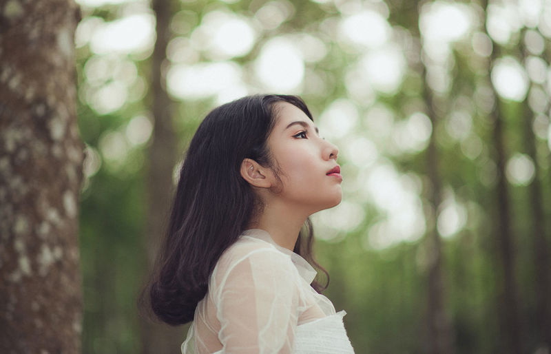 Side view of young woman standing against tree