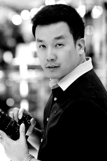 Portrait of man photographing with camera while standing in city at night
