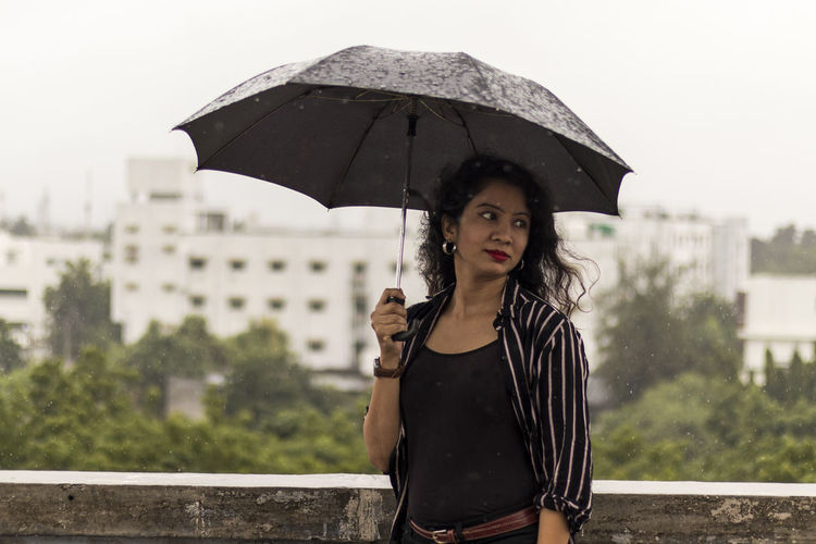 Portrait of woman standing on rainy day