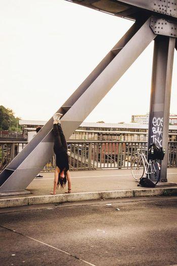 Woman Practicing Headstand On Sidewalk