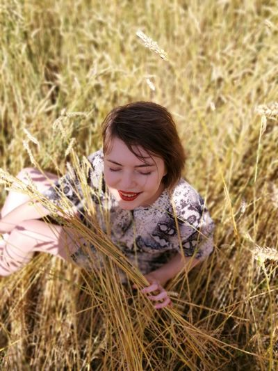 Portrait of a smiling young woman sitting in a field of wheat