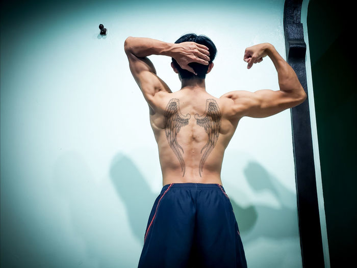 Rear View Of Shirtless Muscular Man Standing Against Wall
