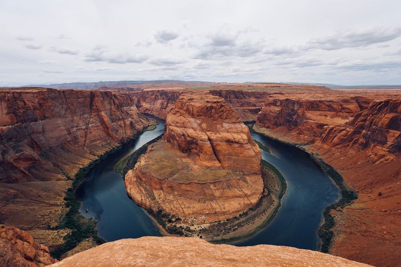 Scenic view of horseshoe bend by river against sky
