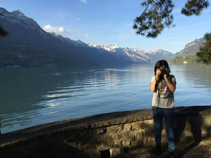 Real People Leisure Activity Water Lifestyles One Person Mountain Beauty In Nature Scenics - Nature Photographing Standing Photography Themes Camera - Photographic Equipment Lake Technology Sky Nature Mountain Range Visual Creativity International Women's Day 2019