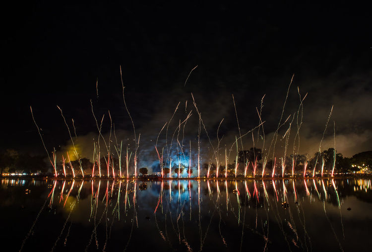 Light trails in lake against sky at night