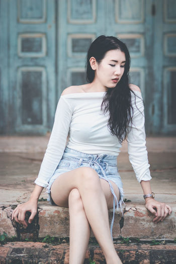 One Person Real People Young Women Young Adult Hair Lifestyles Hairstyle Long Hair Casual Clothing Sitting Beautiful Woman Leisure Activity Day Beauty Three Quarter Length Architecture Women Black Hair Looking Fashion Outdoors Shorts Teenager Asian Teen Asian Woman