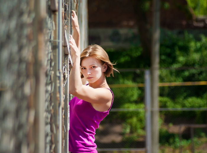Portrait Of Beautiful Young Woman Climbing Wall