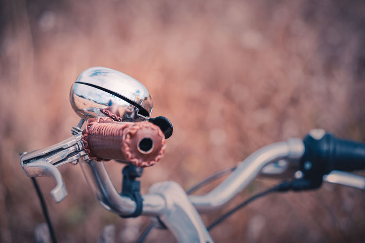 Close-up of a vintage metallic bicycle bell in countryside environment. warm colors