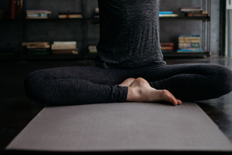 Low section of woman practicing yoga on mat at home