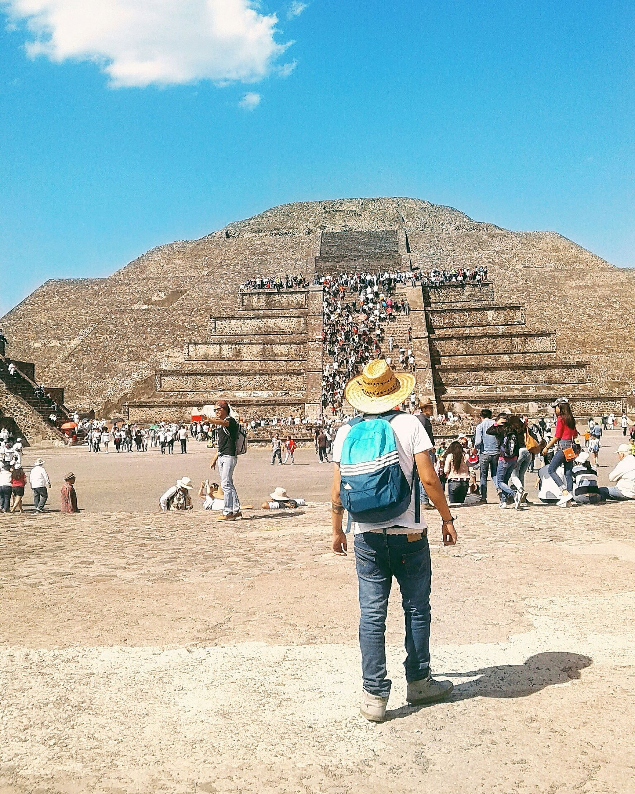 large group of people, real people, tourism, travel destinations, day, leisure activity, history, pyramid, sky, sunlight, lifestyles, ancient, men, outdoors, casual clothing, built structure, nature, travel, vacations, women, architecture, cloud - sky, ancient civilization, old ruin, mountain, blue, arid climate, beauty in nature, people