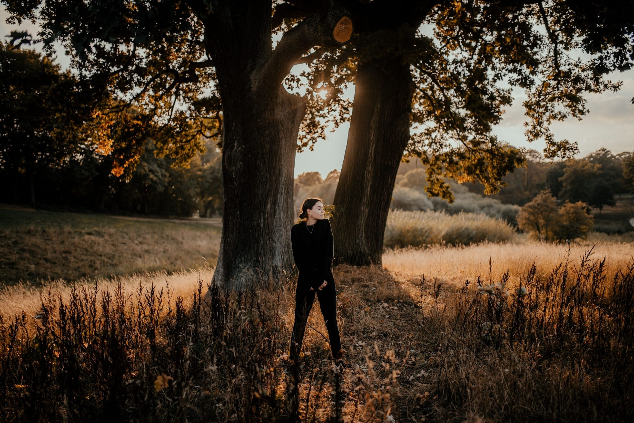 tree, plant, one person, real people, standing, land, lifestyles, field, growth, leisure activity, nature, grass, full length, young adult, non-urban scene, beauty in nature, casual clothing, day, tranquility, outdoors