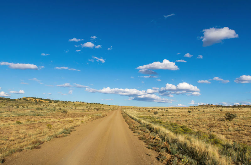 Dirt road amidst land against sky