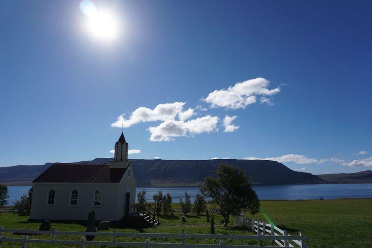 Built structure on landscape against blue sky