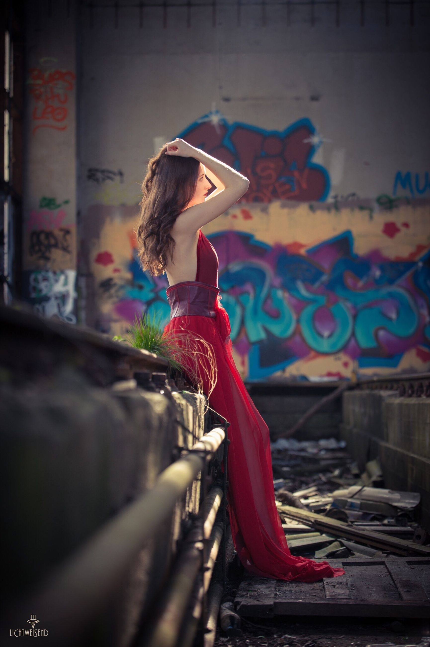 full length, lifestyles, night, men, street, walking, leisure activity, built structure, architecture, rear view, red, casual clothing, graffiti, blurred motion, indoors, person, building exterior, illuminated