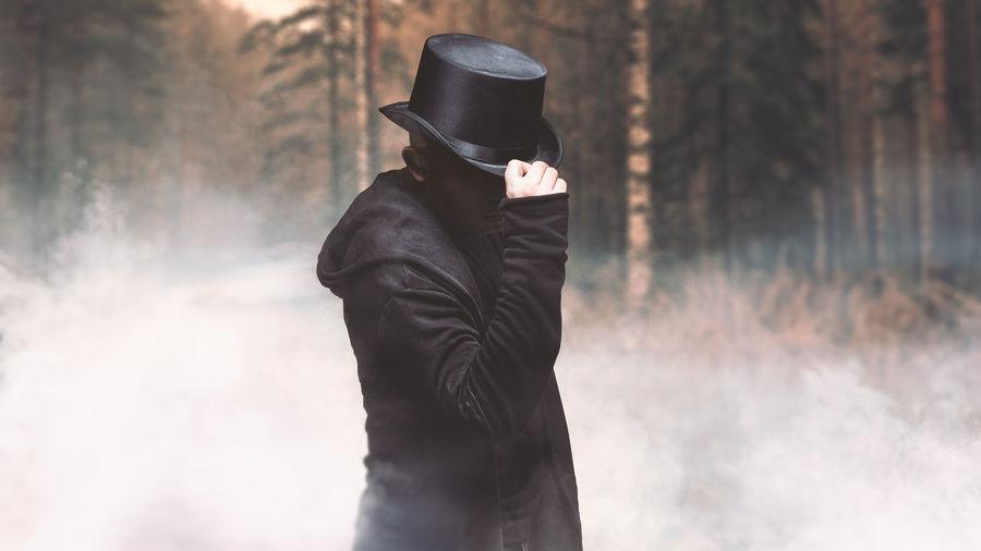 Man wearing hat standing in fog