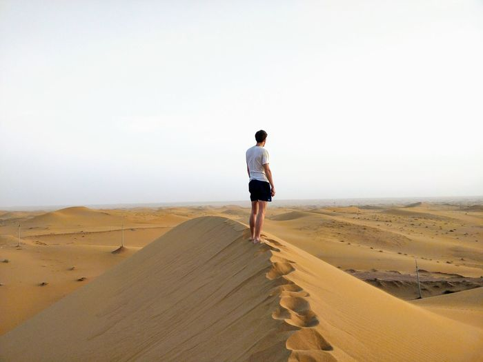 Rear view of man standing on sand dune at desert