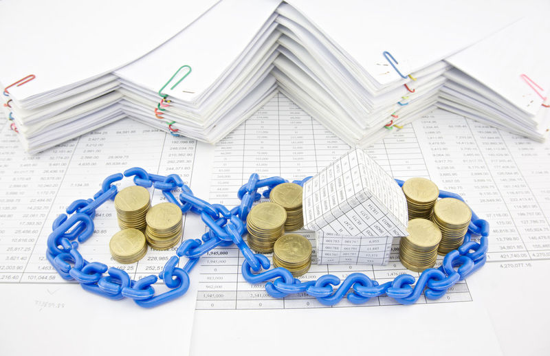 High angle view of chain on coins and model home by stacked papers