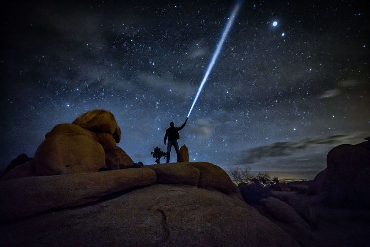 Adult Adventure Astronomy Beauty In Nature Galaxy Joshua Tree National Park Landscape Light Beaming Men Milky Way Mountain Night One Man Only One Person People Rock - Object Science Sitting Sky Space Space And Astronomy Star - Space Star Field Starscape Vacations