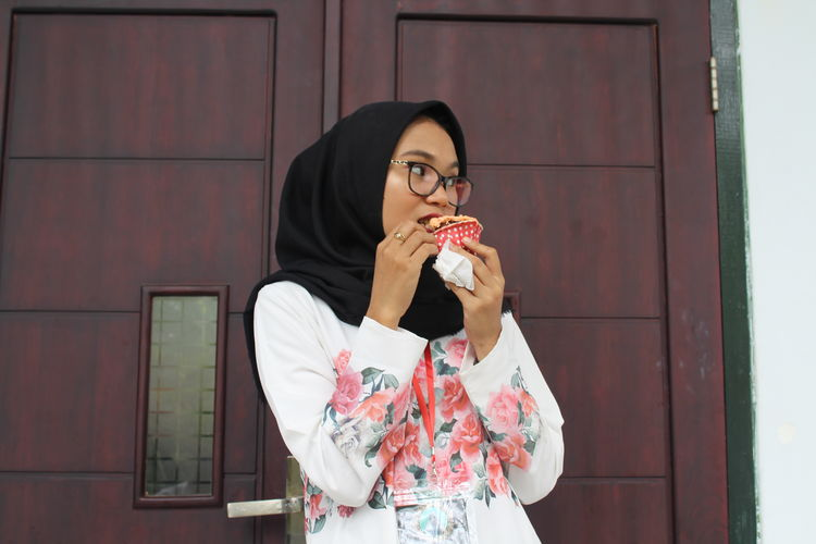 Young woman in hijab eating food while standing against door