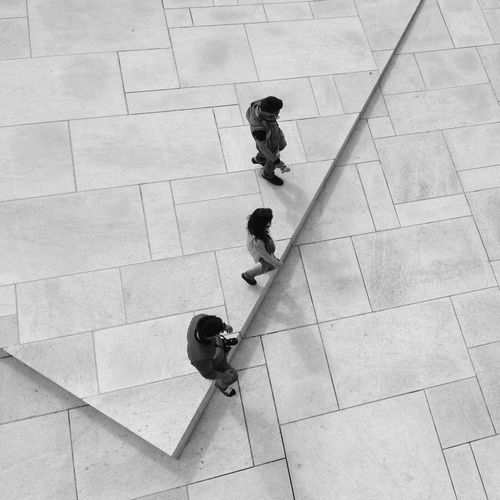 High angle view of people walking on tiled flooring