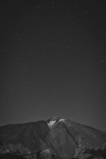Low angle view of snowcapped mountain against sky at night