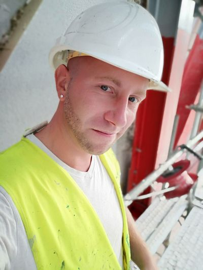 Portrait Of Smiling Young Man Wearing Hardhat At Construction Site