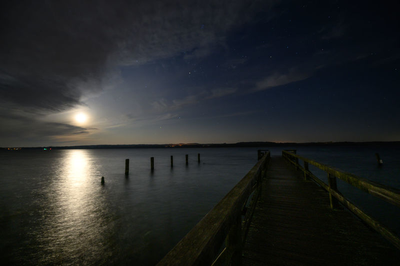 Wooden pier over sea against sky at sunset