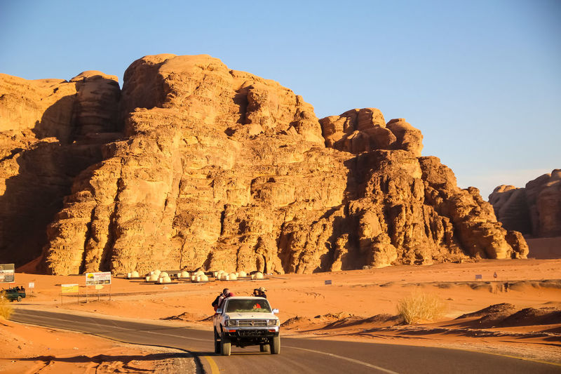 Car on rock formation in desert against clear sky