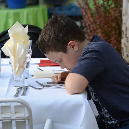 Side View Of Boy Using Smart Phone At Dining Table