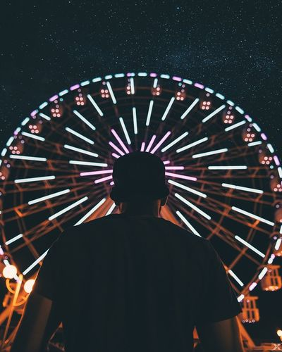 Rear View Of Silhouette Man Standing At Illuminated Amusement Park