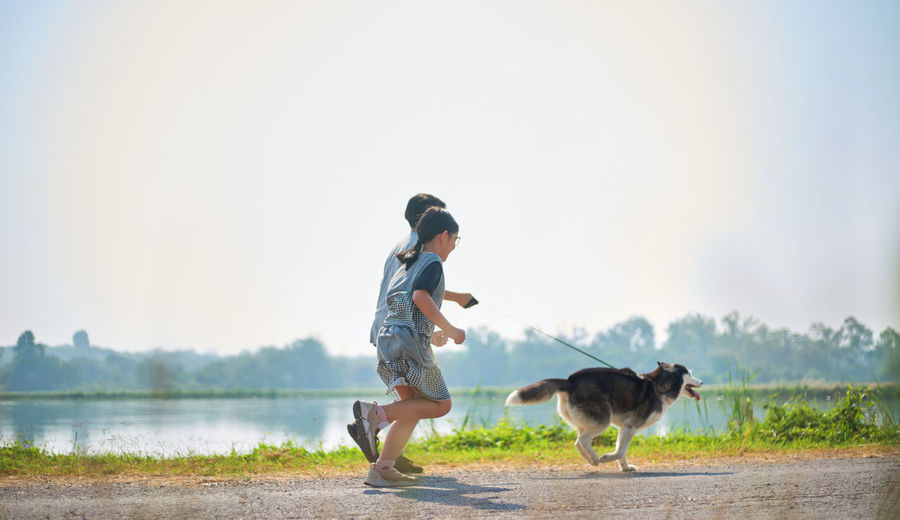 Full length of children playing by lake against sky