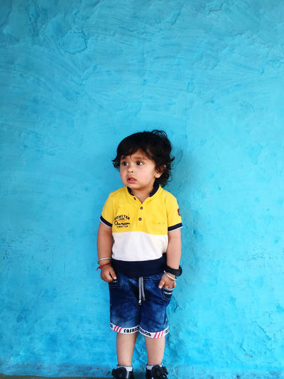 Boy standing against blue wall