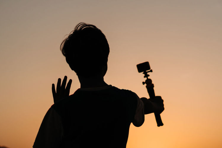 Silhouette man photographing at camera against sky during sunset