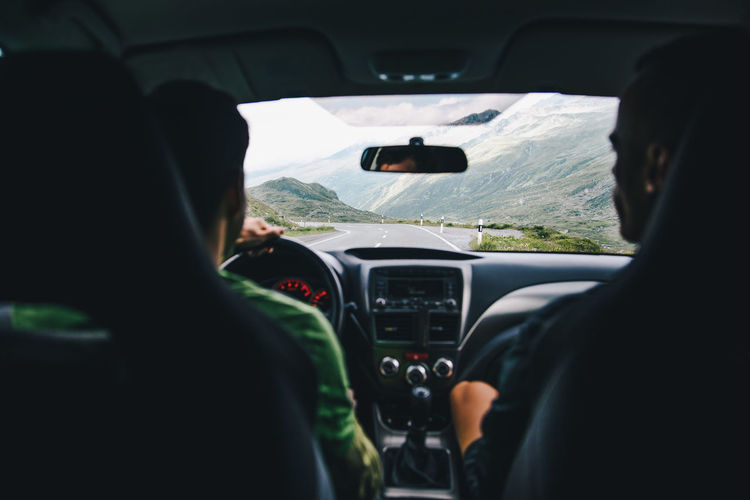 Car Car Interior Dashboard Day Driving Journey Land Vehicle Leisure Activity Lifestyles Men Mode Of Transport Mountain Nature Real People Rear View Road Steering Wheel Transportation Travel Two People Vehicle Interior Windscreen Windshield Connected By Travel