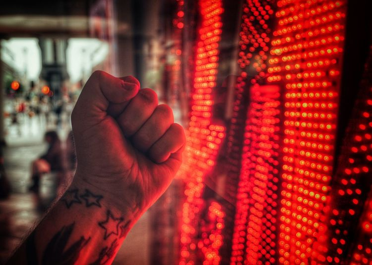 Close-up of hand against illuminated lights