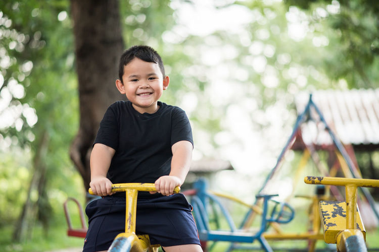Portrait of smiling boy playing on seesaw at playground