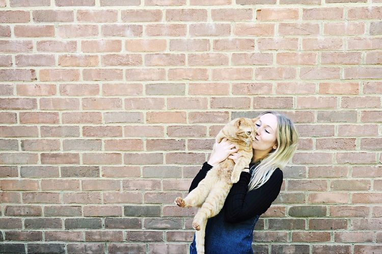 Portrait Of Young Woman Holding And Kissing An Orange Tabby Cat  Against Brick Wall