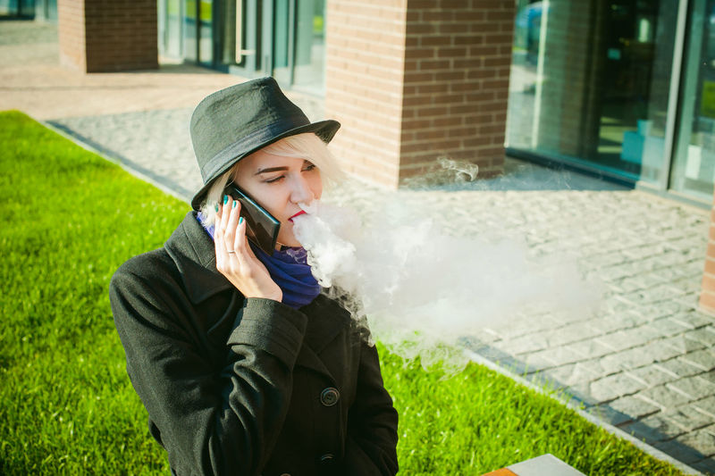 Young Woman Talking On Mobile Phone While Smoking By Built Structure