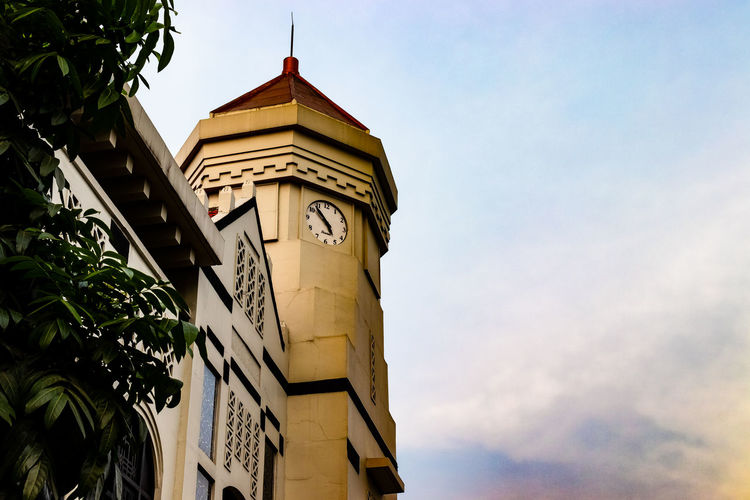 Low angle view of clock tower amidst buildings against sky