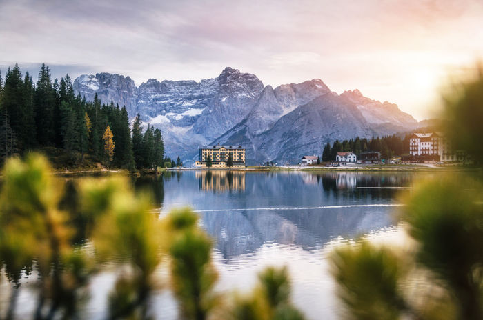 View of Misurina lake with large building of Institute Pius XII through bushes at sunset. Dolomites, Italy. Dolomites Dolomites, Italy Beauty In Nature Dolomiti Italy❤️ Lake Misurina Mountain Mountain Range Nature Outdoors Reflection Scenics Sky Tranquil Scene Tranquility Water Waterfront