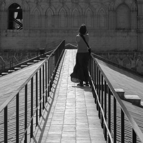Rear view full length of woman standing by building on footbridge