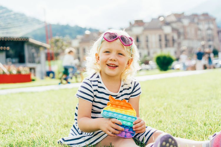 Little happy girl in sunglasses sitting on the lawn with anti-stress pop it smiles.