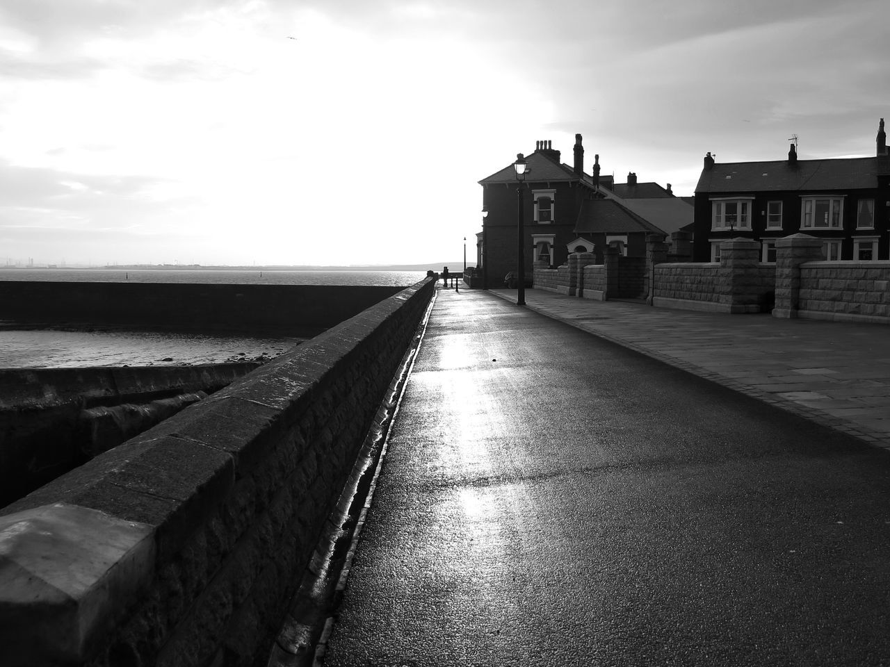 Pathway Leading Towards Sea By Buildings On Sunny Day